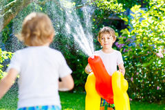 Two little kids boys playing with a garden hose water sprinkler Stock Photos