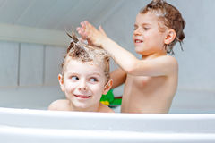 Two little kids boys playing together in bathtub Royalty Free Stock Photos