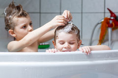 Two little kids boys playing together in bathtub Royalty Free Stock Photography