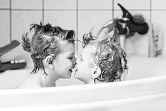 Two little kids boys playing together in bathtub. Happy siblings: Two little twins children playing together with water by taking bath in bathtub at home. Kid stock photos