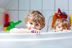 Two little kids boys playing together in bathtub Stock Images