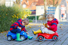 Two little kids boys playing with toy cars, outdoors Royalty Free Stock Images