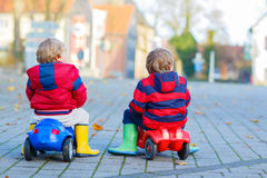 Two little kids boys playing with toy cars, outdoors Stock Photo