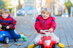Two little kids boys playing with toy cars, outdoors Stock Photos