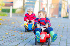 Two little kids boys playing with toy cars, outdoors Royalty Free Stock Image