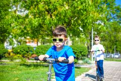 Two little kids boys riding on push scooters. Warn summer or spring day. Brothers kid boy having fun together wearing sunglasses. Friendship concept stock images