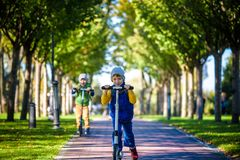 Two little kids boys riding on push scooters. Warn summer or spring day. Brothers kid boy having fun together wearing sunglasses. Friendship concept royalty free stock image