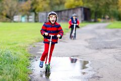Two little kids boys riding on push scooters on the way to or from school. Schoolboys of 7 years driving through rain stock photos