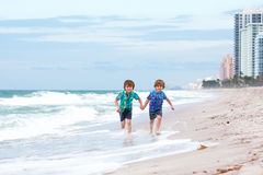 Two little kids boys running on the beach of ocean Stock Images