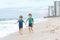 Two little kids boys running on the beach of ocean. Two happy little kids boys running on the beach of ocean. Funny cute children, sibling and best friends Stock Photography