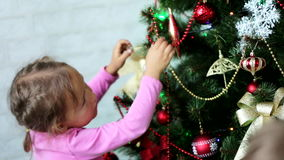 Two little kids brother and sister decorating Christmas tree at daytime stock footage