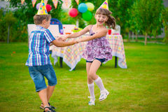 Two little kids dancing roundelay. Two little kids celebrating birthday dancing roundelay Stock Images