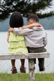 Two little kids dating in a park. Two little kids dating with hand lifts onto shoulder in a park Royalty Free Stock Photos
