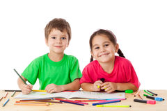 Two little kids draw with crayons. Two smiling little kids at the table draw with crayons, isolated on white Stock Images