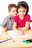 Two little kids draw for mum. Two little kids at the table draw with crayons for mum,  on white Royalty Free Stock Photos