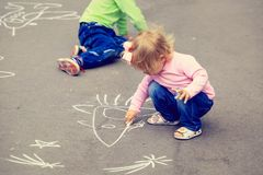 Two little kids drawing on asphalt outdoors Stock Photography