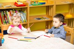 Two little kids drawing with colorful pencils in preschool at the table. Stock Image