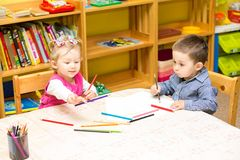 Two little kids drawing with colorful pencils in preschool at the table. Little girl and boy drawing in kindergarten royalty free stock photos