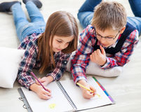 Two little kids drawing with crayons Royalty Free Stock Image
