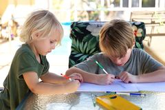 Two Little Kids Drawing on Paper Outside by Pool on Summer Day. Two little kids are sitting under the Lanai by the pool, drawing a picture on paper with colored stock photos