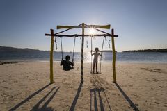 Two little kids enjoy sunset view on a swing stock photo