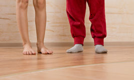 Two Little Kids Feet on Wooden Floor Stock Photos