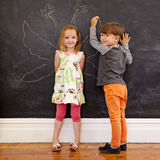Two little kids in front of blackboard with angel wings. Full length portrait of cute little girl standing and little boy drawing angel wings around her on Royalty Free Stock Photography