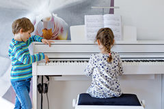 Two little kids girl and boy playing piano in living room or music school. Preschool children having fun with learning to play music instrument. Education Royalty Free Stock Photos