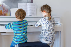 Two little kids girl and boy playing piano in living room or music school. Preschool children having fun with learning to play music instrument. Education Stock Image