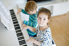Two little kids girl and boy playing piano in living room or music school. Preschool children having fun with learning to play music instrument. Education Stock Photography