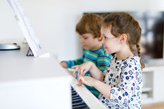 Two little kids girl and boy playing piano in living room or music school. Preschool children having fun with learning to play music instrument. Education Royalty Free Stock Images