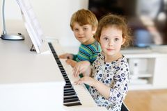 Two little kids girl and boy playing piano in living room or music school. Preschool children having fun with learning to play music instrument. Education Stock Images
