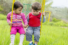 Two little kids having fun on a swing on summer day Royalty Free Stock Photography