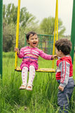 Two little kids having fun on a swing. On summer day Royalty Free Stock Photo