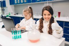 Two little kids in lab coat learning chemistry in school laboratory. Young scientists in protective glasses making. Experiment in lab or chemical cabinet royalty free stock image