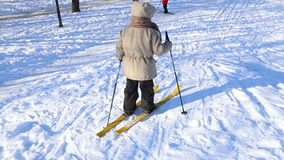 Two little kids learning to ski. On the hill in city stock footage