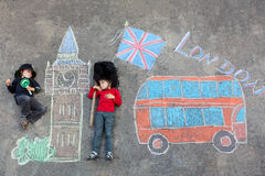 Two little kids with London picture drawing with chalks Royalty Free Stock Photo