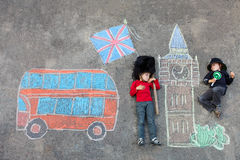 Two little kids with London picture drawing with chalks. Two funny little friends boys in british queen's guard soldier and policeman uniform having fun with Stock Photos