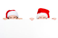 Two little kids looking over white poster in red Santa hats. Stock Image