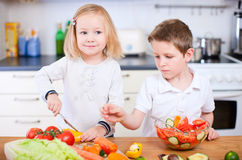 Two little kids making salad Stock Photos