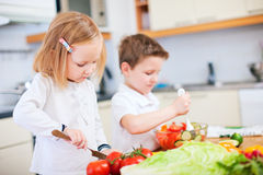 Two little kids making salad Royalty Free Stock Photos
