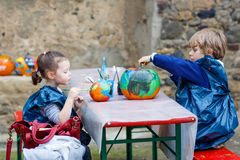 Two little kids painting with colors on pumpkin Stock Photo