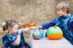 Two little kids painting with colors on pumpkin Royalty Free Stock Photography