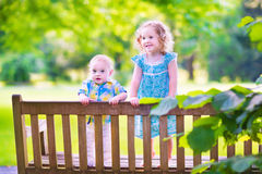 Two little kids on a park bench. Adorable kids, little curly girl and a cute baby boy, brother and sister, sitting together on a wooden bench in a garden royalty free stock photo