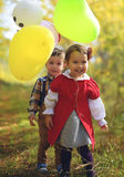 Two little kids playing with balloons in the park Royalty Free Stock Images