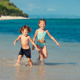 Two little kids playing at the beach Stock Photos