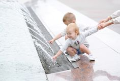 Two little kids playing in the city square fountain. Children hold mummy by a hand. stock image