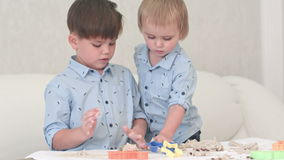 Two little kids playing with dough and learning how to bake. Professional shot in 4K resolution. 092. You can use it e.g. in your commercial video, business stock footage