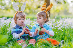 Two little kids playing with Easter chocolate bunny Stock Photos