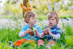 Two little kids playing with Easter chocolate bunny Stock Images